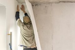 Young man, worker glueing wallpapers on concrete wall. Repair the apartment. Home renovation concept. White Wallpaper. Young man, worker glueing wallpapers on royalty free stock photos