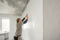Young man, worker glueing wallpapers on concrete wall. Repair the apartment. Home renovation concept. White Wallpaper. Young man, worker glueing wallpapers on stock images