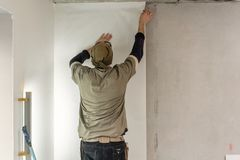 Young man, worker glueing wallpapers on concrete wall. Repair the apartment. Home renovation concept. White Wallpaper. Young man, worker glueing wallpapers on stock photo
