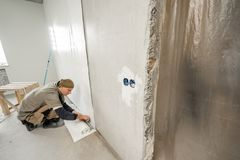 Young man, worker glueing wallpapers on concrete wall. Repair the apartment. Home renovation concept. White Wallpaper. Young man, worker glueing wallpapers on royalty free stock photo