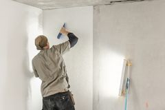 Young man, worker glueing wallpapers on concrete wall. Repair the apartment. Home renovation concept. White Wallpaper. Young man, worker glueing wallpapers on royalty free stock photography