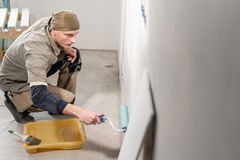 Young man, worker glueing wallpapers on concrete wall. Repair the apartment. Home renovation concept. White Wallpaper. Young man, worker glueing wallpapers on royalty free stock image