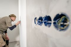 Young man, worker glueing wallpapers on concrete wall. Repair the apartment. Home renovation concept. White Wallpaper. Young man, worker glueing wallpapers on royalty free stock images