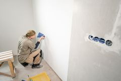 Young man, worker glueing wallpapers on concrete wall. Repair the apartment. Home renovation concept. White Wallpaper. Young man, worker glueing wallpapers on stock photography