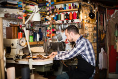 Young man worker qualitatively stitching belt. In leather workshop Stock Images
