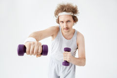 Young man working on arm muscles training with  dumbbells Royalty Free Stock Photo