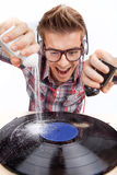 Young man working as dj with ear-phones and glasses. Royalty Free Stock Image