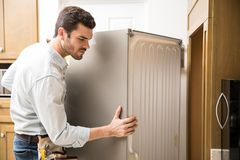 Electrician moving a fridge in a kitchen. Young man working as an electrician exposing the back of a fridge to check and repair it stock images