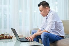 Man typing on laptop. Young man working as a freelancer at home, he sitting on couch and typing on laptop stock images