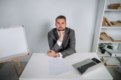 A young man is working behind a laptop in his office. The teacher prepares for the lecture. A young man is bored in the workplace. The teacher prepares for the Royalty Free Stock Photos