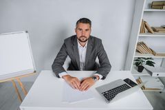 A young man is working behind a laptop in his office. The teacher prepares for the lecture. A businessman in gray suit works at the computer Royalty Free Stock Photo