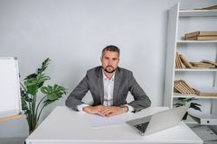 A young man is working behind a laptop in his office. The teacher prepares for the lecture. A businessman in gray suit works at the computer Royalty Free Stock Photos