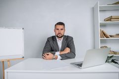 A young man is working behind a laptop in his office. The teacher prepares for the lecture. A businessman in gray suit works at the computer Royalty Free Stock Images