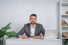 A young man is working behind a laptop in his office. The teacher prepares for the lecture. A businessman in gray suit works at the computer Royalty Free Stock Image