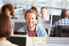 Young man working in a call centre, looking to camera Royalty Free Stock Photos