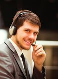 Young man working at callcenter, using headset. Happy young man working at callcenter, using headset Stock Image
