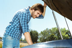 Young man working on a car engine Stock Photography