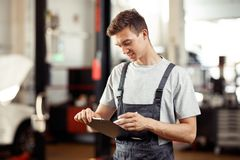 A young man working at a car repair service is filling in a form stock image