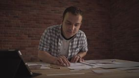 Young man working carefully attentively concentrated on small detail of paper work business project on wooden table. People working on project in business office stock video footage
