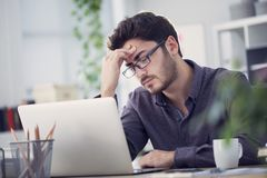Young man working on computer and having headache royalty free stock photos