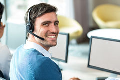 Young man working on computer with headset. Portrait of a young man working on computer with headset in office Stock Photography
