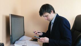 Young man is working at computer and mobile phone sitting on a leather chair. Young man is working at computer and mobile phone sitting on a leather chair stock video footage