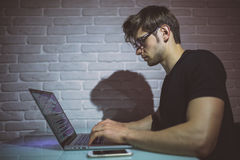 Young man working on computer at night in dark office. The designer works in the later time. Hacker Royalty Free Stock Photo