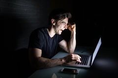 Young man working on computer at night in dark office the designer works in the later time. Hacker Royalty Free Stock Images
