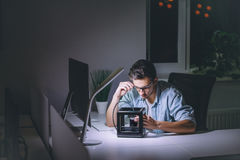Young man working on computer at night in dark office stock image