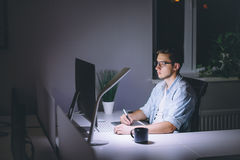 Young man working on computer at night in dark office Royalty Free Stock Photo