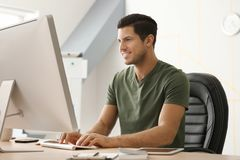 Young man working with computer. In office Royalty Free Stock Photography