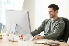 Young man working with computer. At table in office Royalty Free Stock Image
