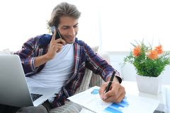 Young man working with financial documents at home. Royalty Free Stock Image