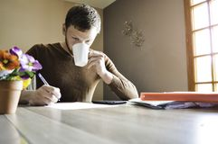 Young man working paperwork and bills at home and drinking coffee stock images
