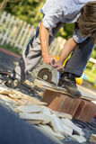 Young man working in his back yard using circular saw Stock Photo