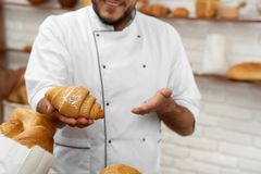 Young man working at his bakery. Cropped shot of a cheerful professional baker smiling holding out delicious fresh croissant offering to the viewer copyspace Stock Photo