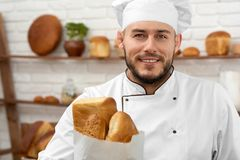 Young man working at his bakery royalty free stock images