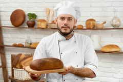 Young man working at his bakery. Horizontal shot of a handsome bearded young professional baker in uniform posing at his bakery with a loaf of delicious freshly Stock Photo