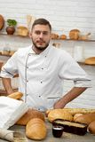 Young man working at his bakery. Vertical portrait of a professional baker posing at his bakery shopping selling buying food pastry delicious healthy natural Stock Image