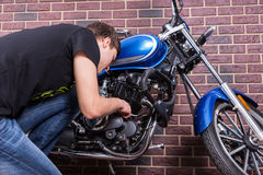 Young Man Working on his Blue Custom Motorcycle Stock Image