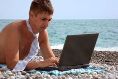 Young man working on his laptop on beach Stock Image