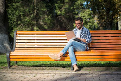 Young man working on his laptop on the bench outdoors Stock Image