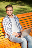 Young man working on his laptop on the bench outdoors Royalty Free Stock Image