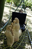 Young man working on his laptop in hammock. Young barefoot man lying in hammock surfing Internet in shade of tropical trees Royalty Free Stock Image