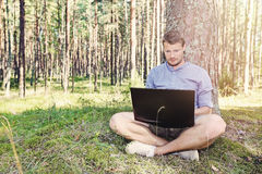 Young man working with his laptop outdoors. In nature stock image