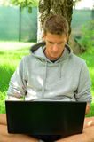 Young man working on his laptop under the tree Royalty Free Stock Images