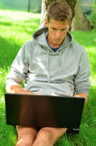 Young man working on his laptop under the tree Royalty Free Stock Photo