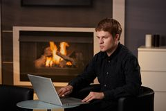 Young man working at home. Young man sitting in front of fireplace at home on a cold winter day, working on laptop computer Royalty Free Stock Photos