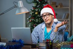 The young man working at home on christmas day Stock Images