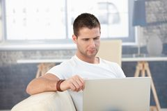 Young man working at home on laptop Stock Photo